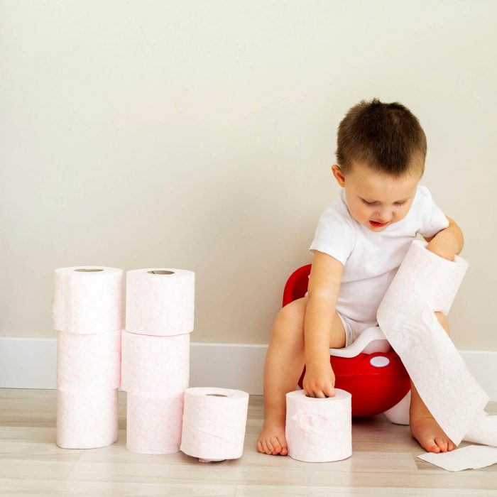 Small,Boy,Toddler,Sitting,On,Red,Potty,And,Playing,With
